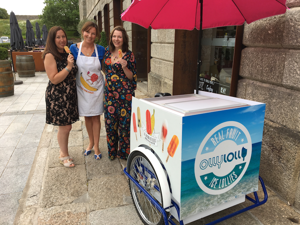 three women at an ice lolly stand eating