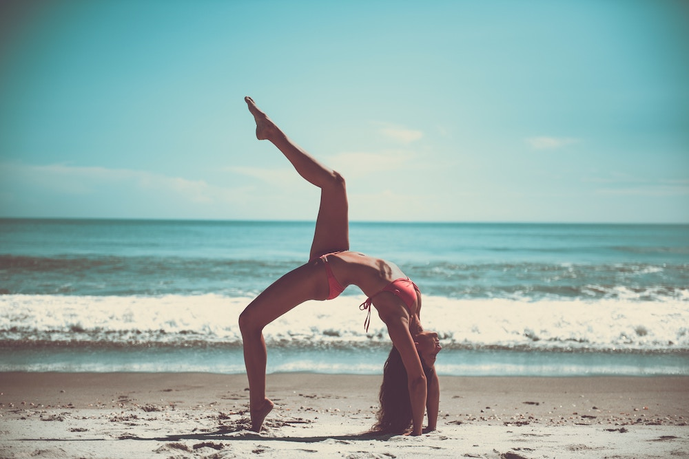 woman doing yoga pose on a beach