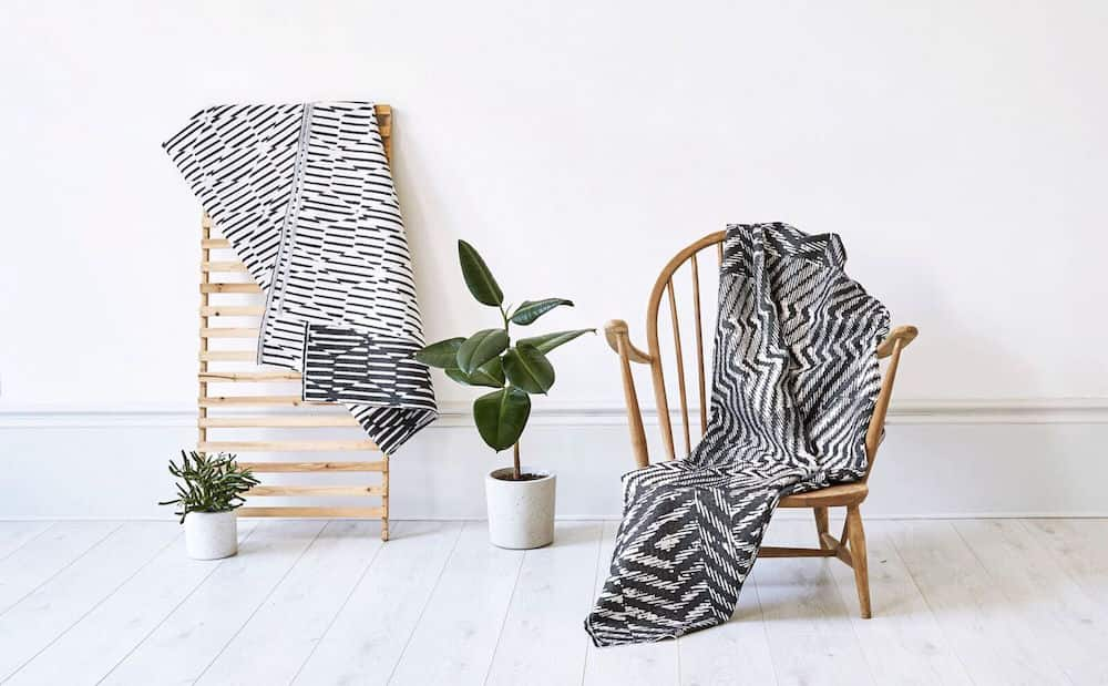 striped throws wooden armchair green plants