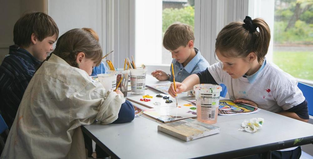 group of children sat at a table painting