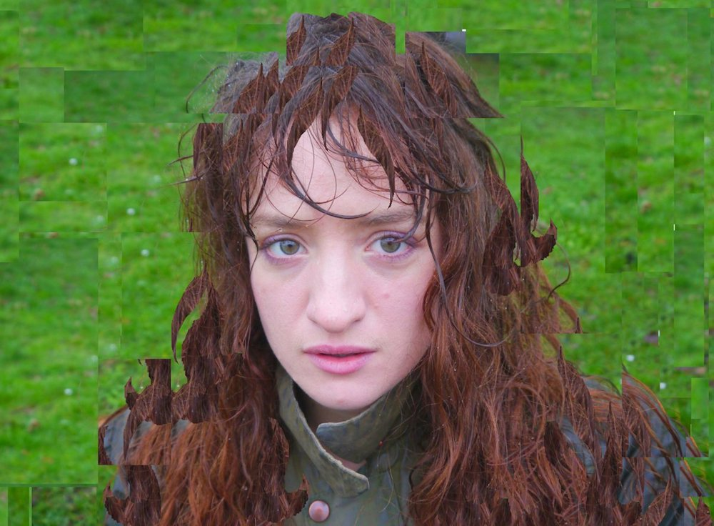 girl with red hair and pale skin in a green field