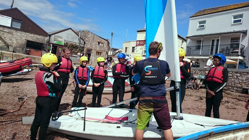 group of children dressed in waterproof sailing kit learning to sail