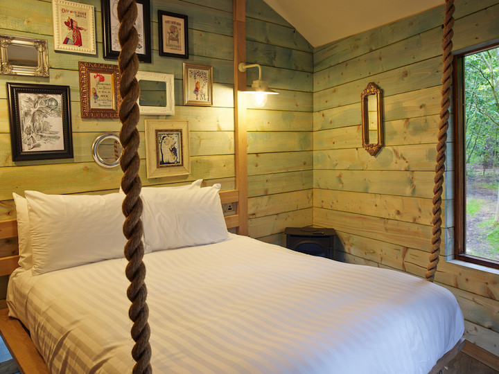 interior of a log cabin with funky art hung on wooden cladded walls
