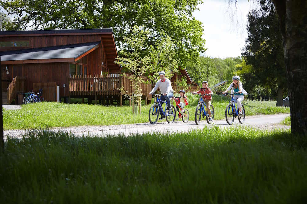 family cycling in the forest outside a log cabin