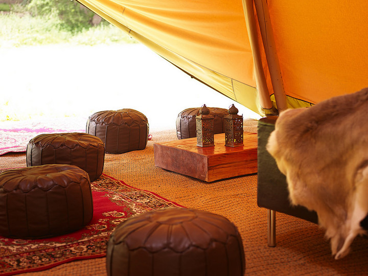 interior of tent with leather pouffe and throws