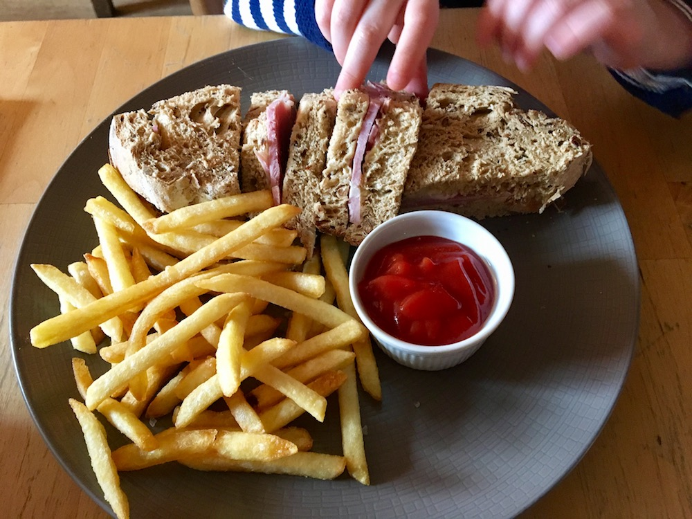ham sandwich with chips and tomato sauce