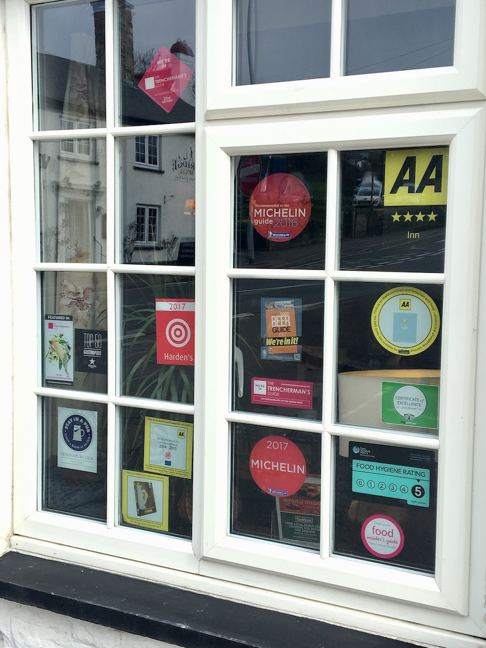 window of pub with award stickers from Michelin, the AA, Tripadvisor