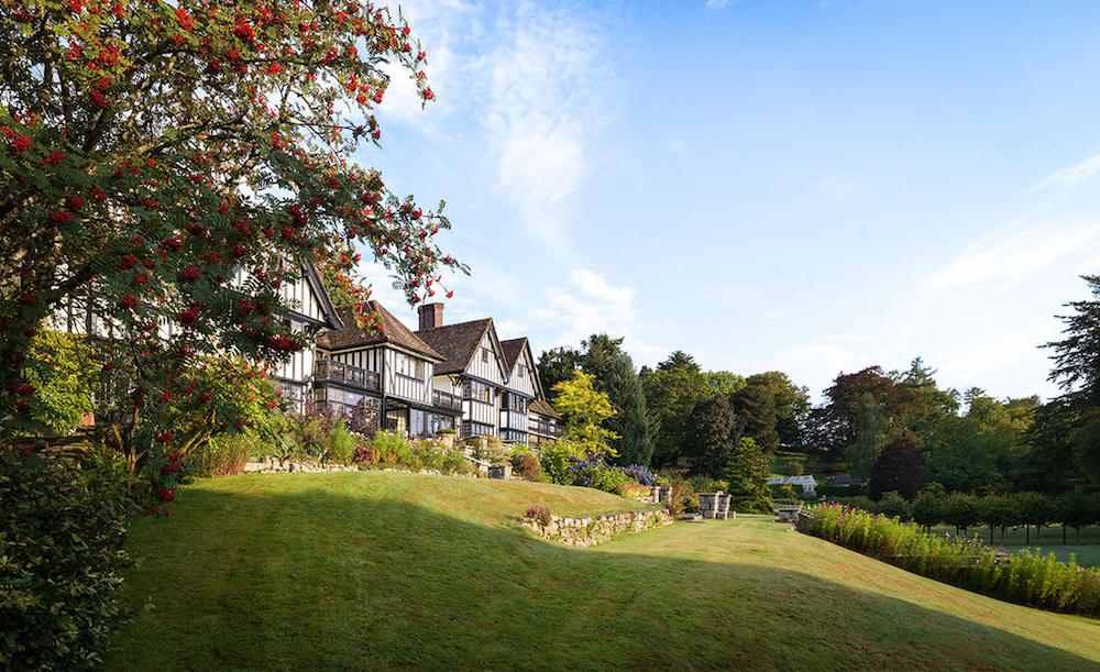 Exterior of country house hotel with mock tudor front and gardens, blue sky