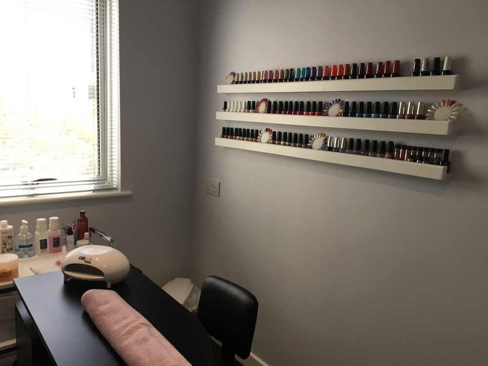interior of nail salon room with nail polishes lined up on shelf