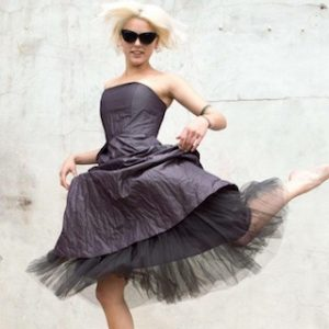 Woman with blonde hair and sunglasses wearing a black dress with tulle underskirt against a wall