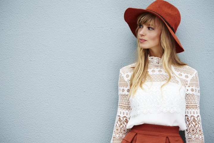 woman in red hat and matching skirt, with white lace top against a powder blue wall
