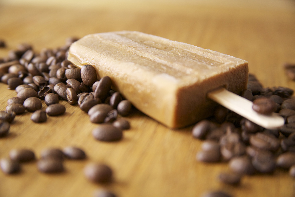 coffee flavoured ice lolly on table surrounded by coffee beans