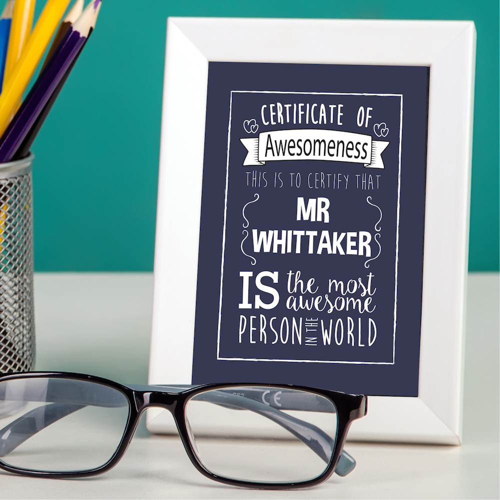 personalised poster in a white frame against teal background with glasses and pencil pot