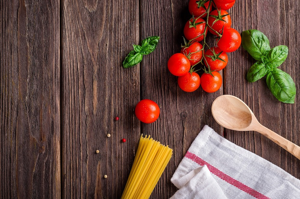 tomatoes, spaghetti, basil, wooden spoon and teatowel on wooden table