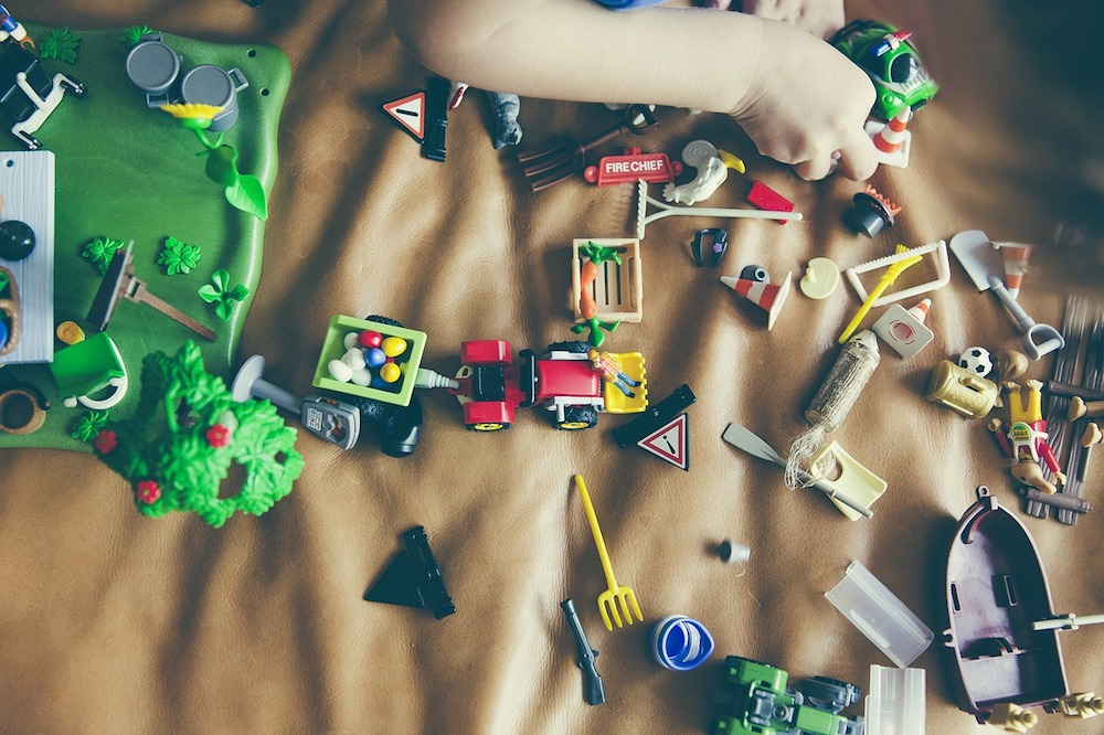 top shot looking down on a blanket with toy cars and boats strewn all over
