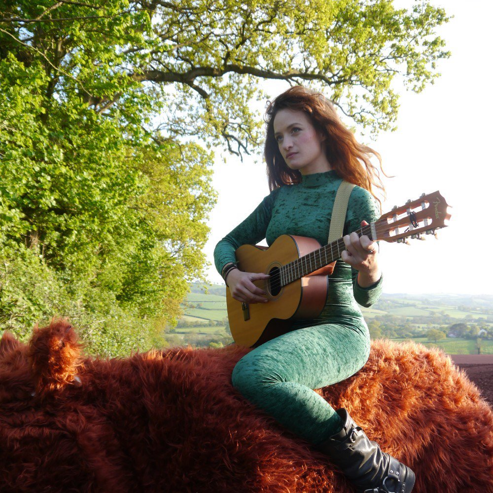 girl with red hair and green cat suit on a cow playing guitar in a field