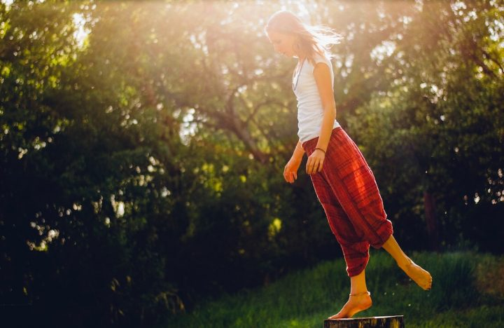 Woman in red yoga pants doing yoga in a garden with dappled sunlight