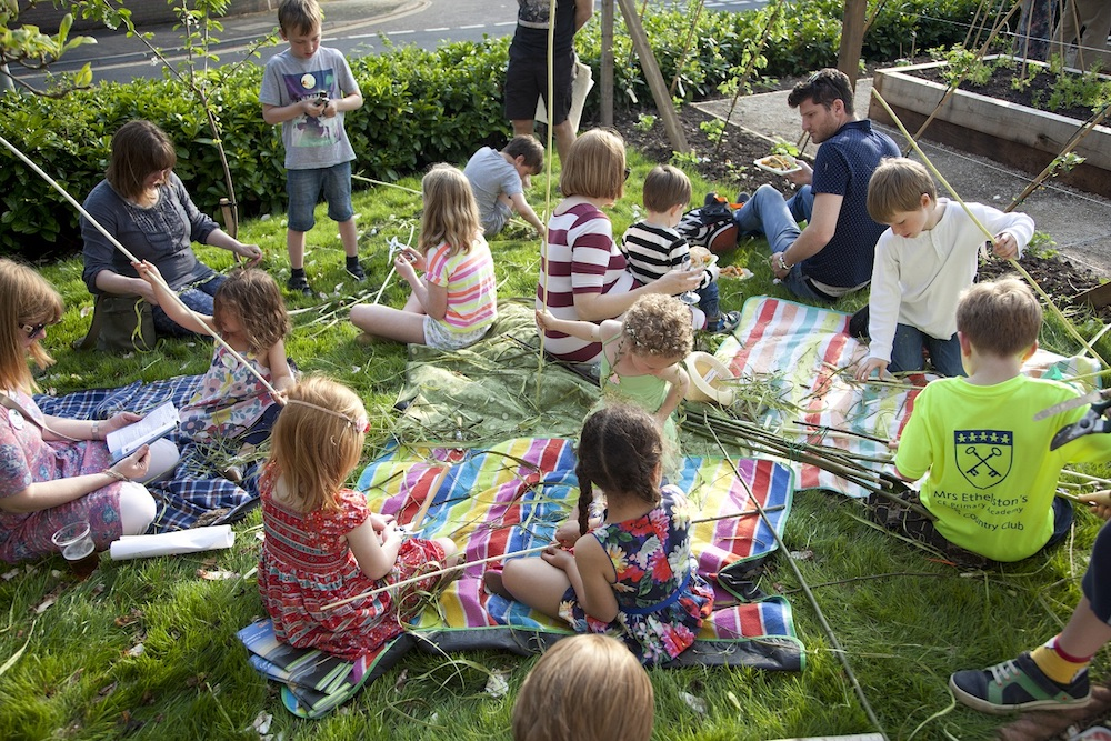 children sat on grass making things from willow