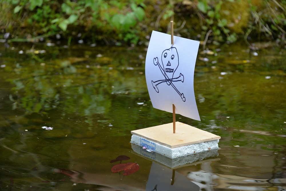 small, handmade boat with skull and crossbones on the mast floating in a river