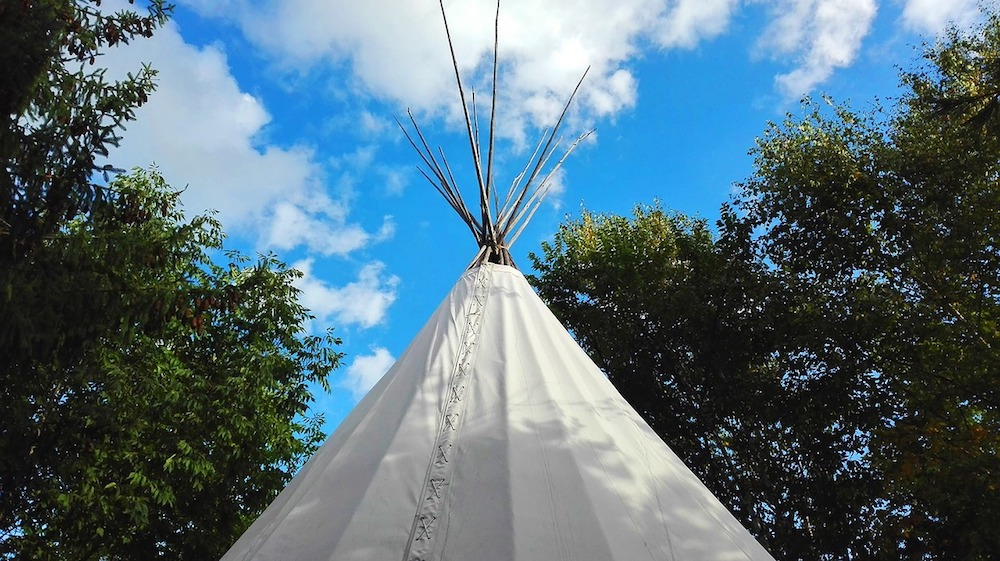 top of a white wigwam or tipi against trees and blue sky with white fluffy clouds