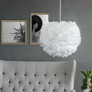 white feather lampshade against grey sofa and grey walls with art and green plant