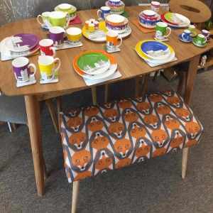 upholstered bench in fox print with wooden table and coloured crockery