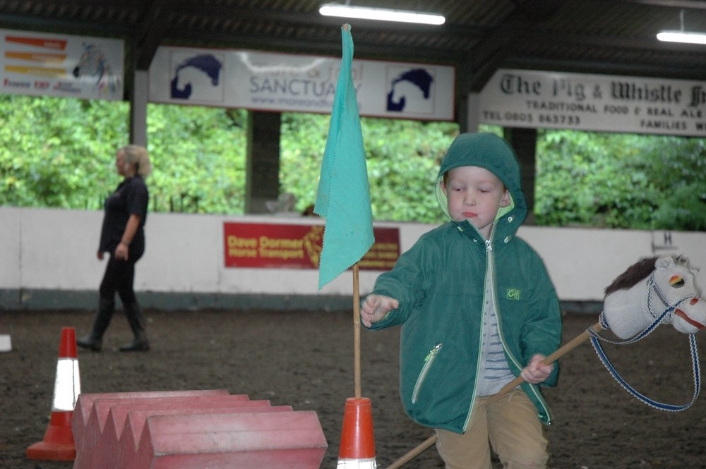 little boy in green coat with a hobby horse