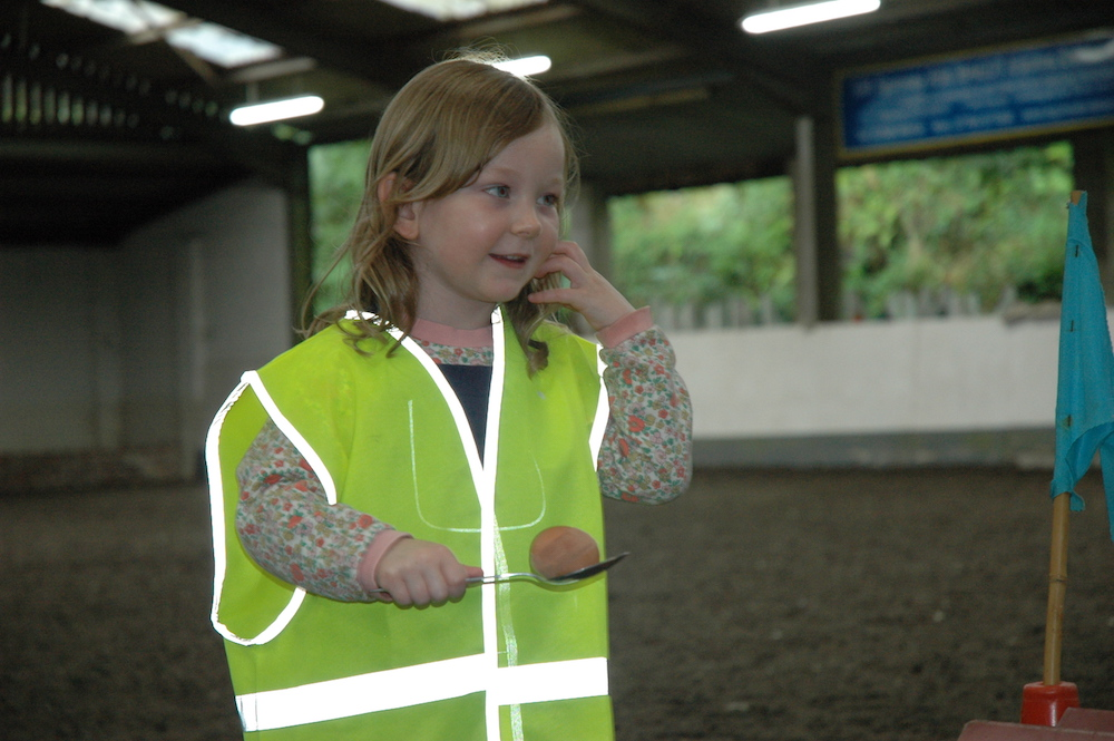 little girl in high vis jacket carrying an egg and spoon