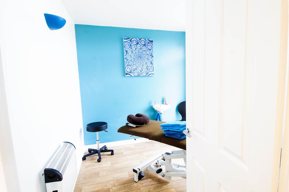 treatment room at hands on clinic with blue walls and massage bed