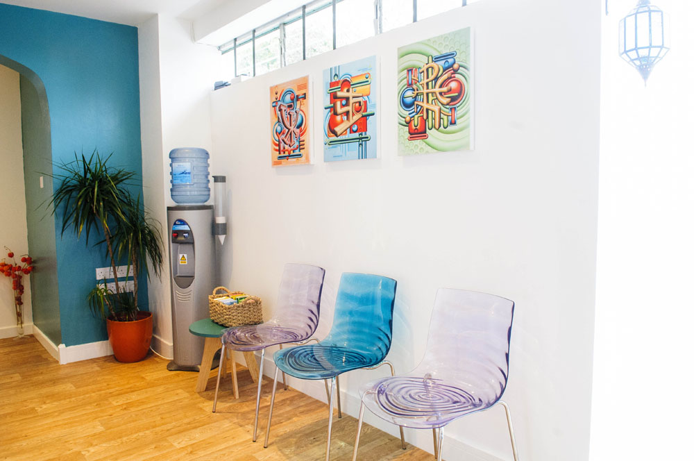 colourful perspex chairs and colourful art on white walls