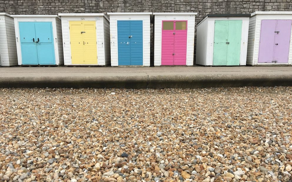 colourful beach huts and pebble beach in lyme regis seafront