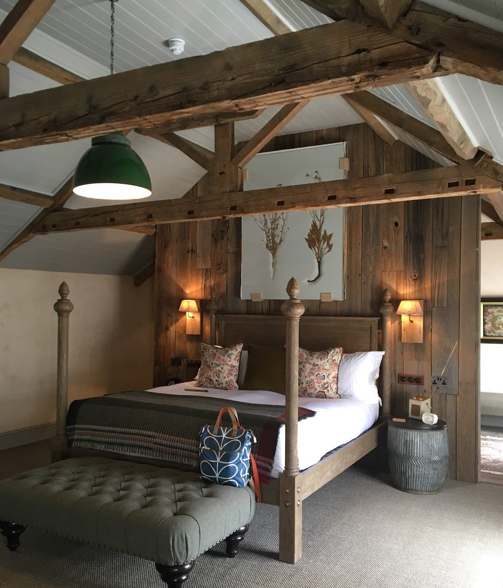 hotel bedroom with wooden pannelling and four poster bed