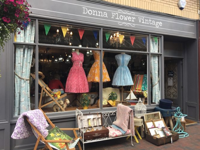 Exterior of vintage shop Donna Flower Vintage with pink, orange and blue dresses on mannequins, vintage furniture, colourful bunting and grey painted exterior