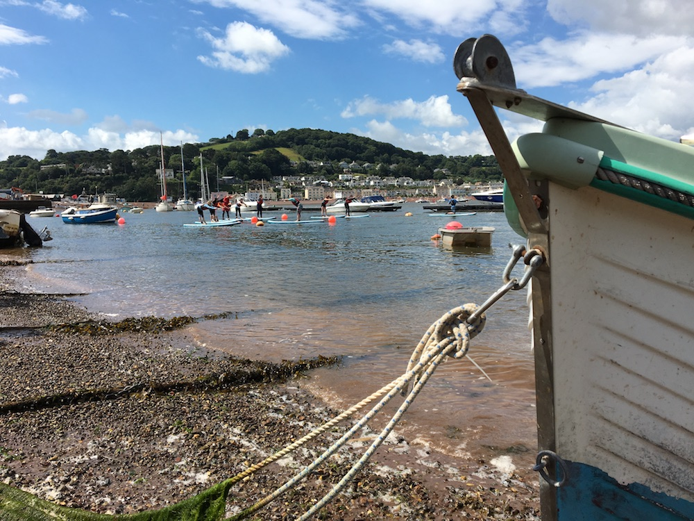 Teignmouth back beach with boats and paddle boarders