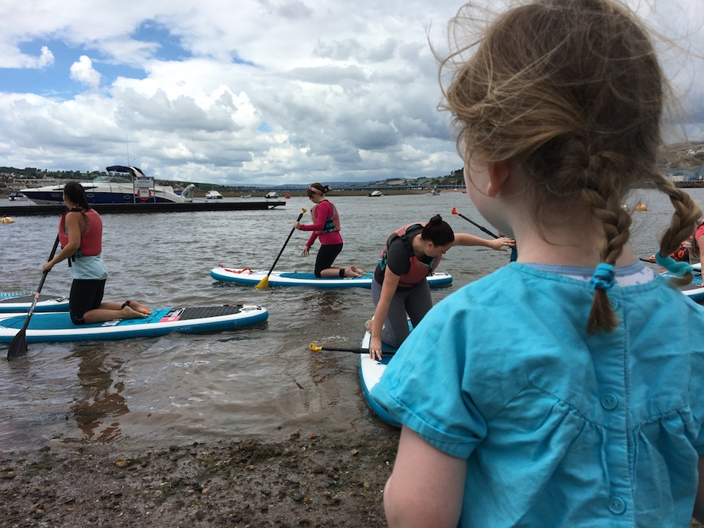 small girl in blue dress watching stand up paddle board yoga