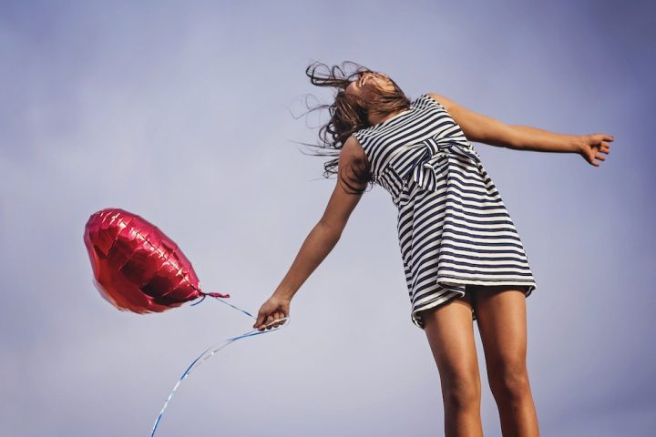 girl in summer dress with red balloon