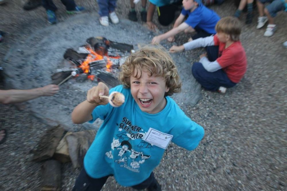boy toasting marshmallows around campfire