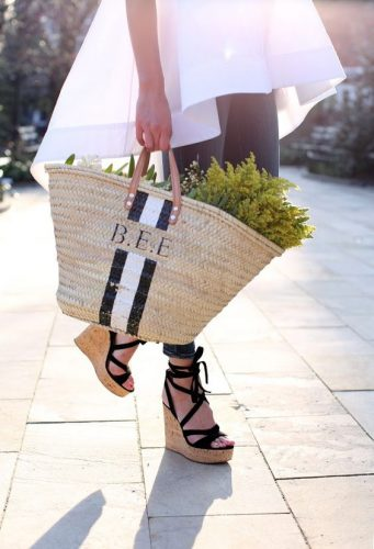 woman in black wedge heels carrying large basket handbag with BEE initials and black and white stripe, with flowers in the bag, walking along street