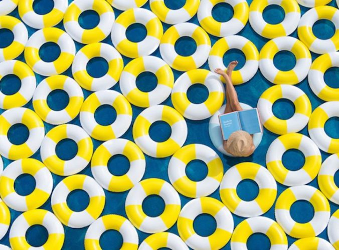 several rubber rings in a swimming pool with woman sat in one reading a book