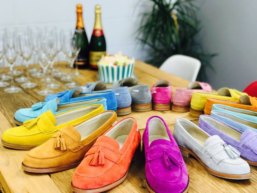 orange, purple, yellow, grey, turquoise, sky blue suede loafers on a table with champagne