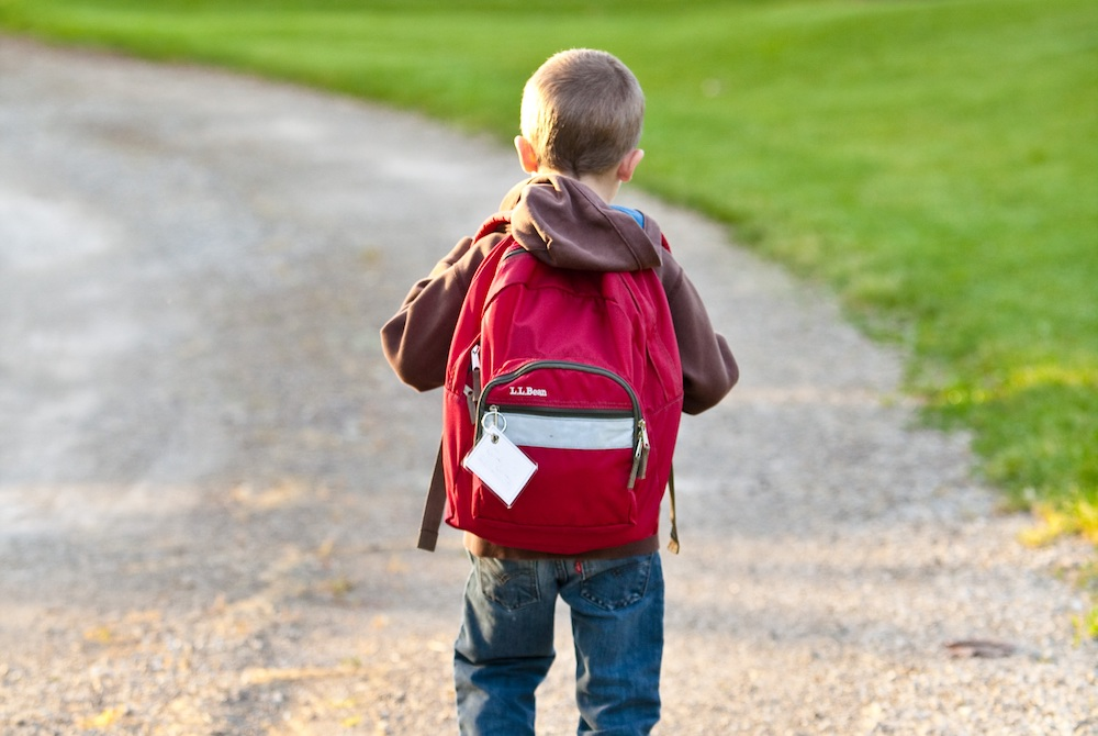 boy with red bag going to school