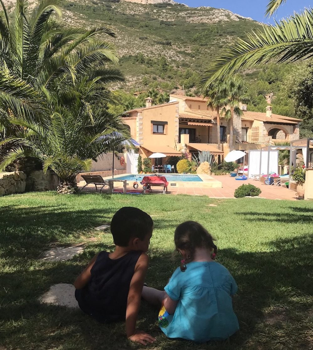 children sat on grass with villa and pool in background