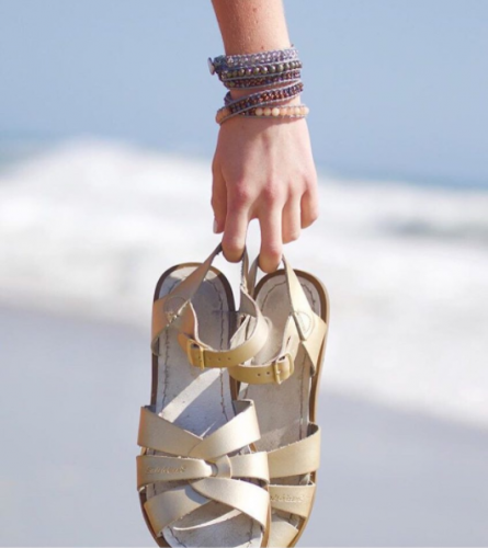 woman holding gold sandals walking along beach