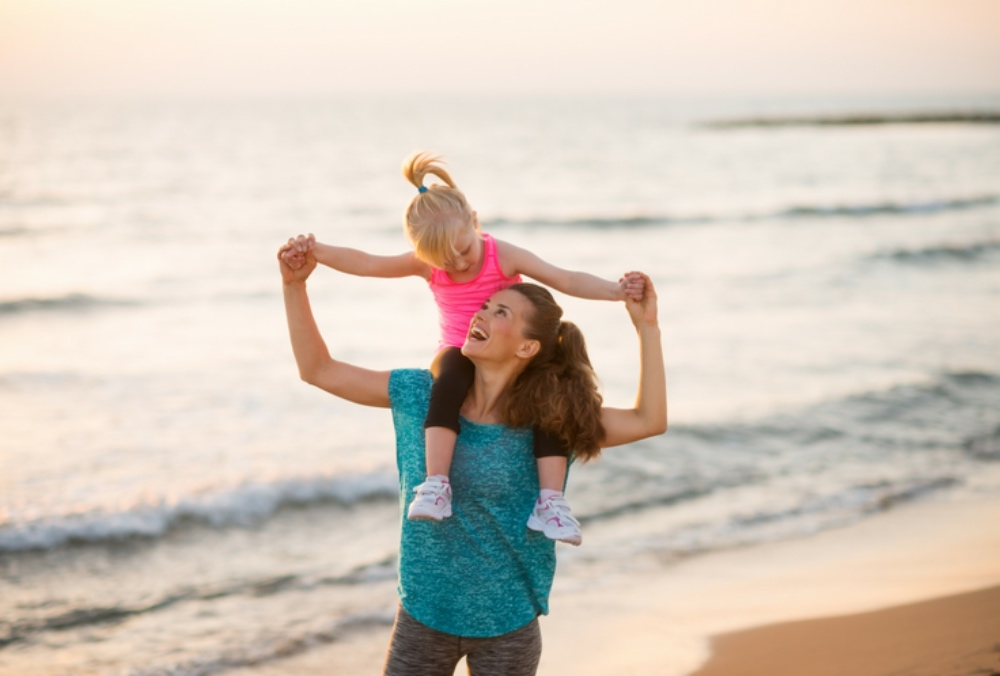 woman walking on beach with girl on her shoulders