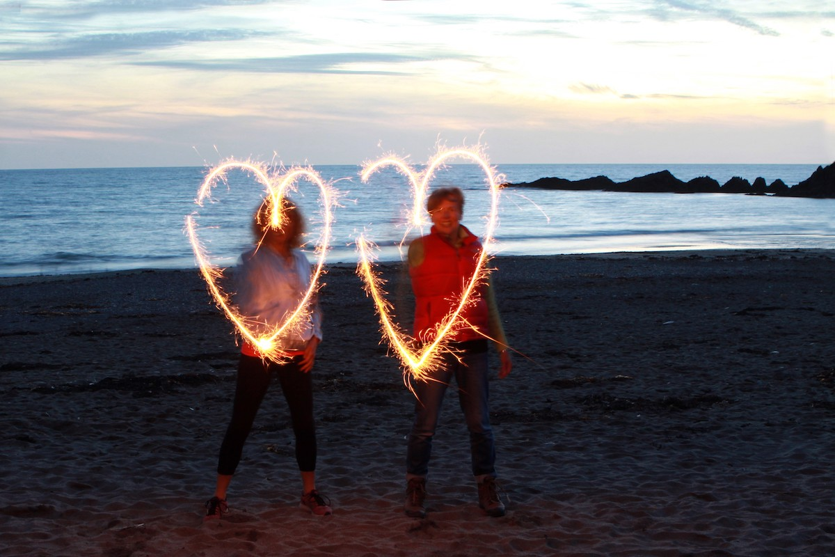 Heart and Sole Retreats sun setting on beach women holding sparklers making heart shape in air