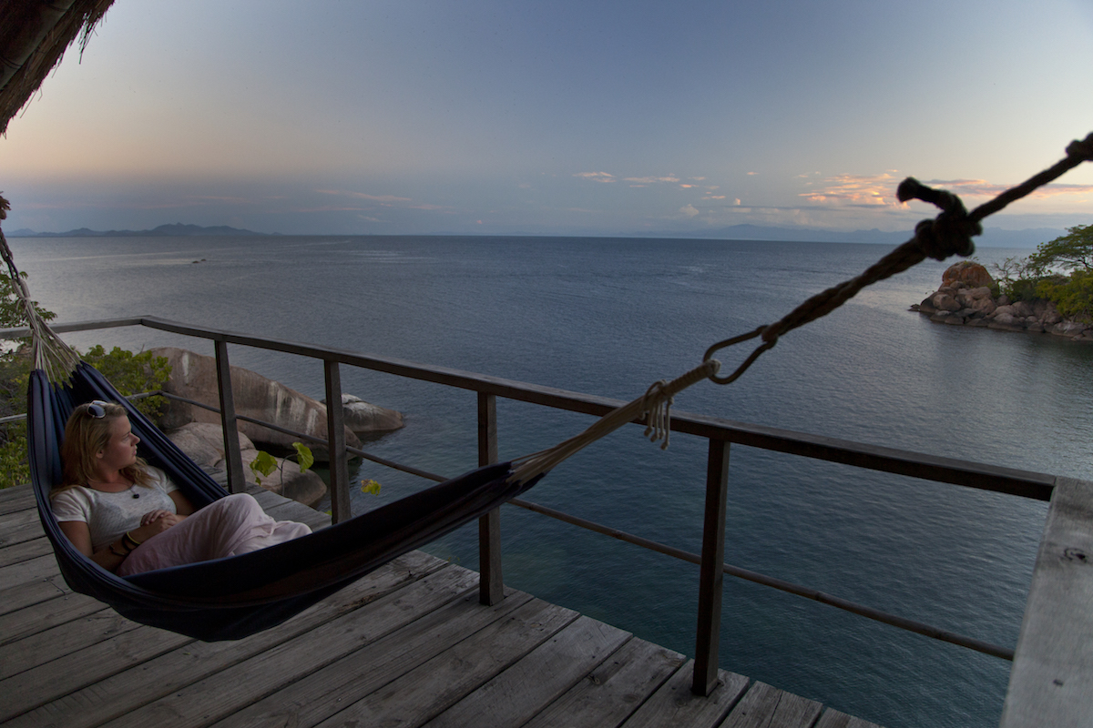 Women's Expedition Orbis Malawi women laying in hammock on wood balcony overlooking sea