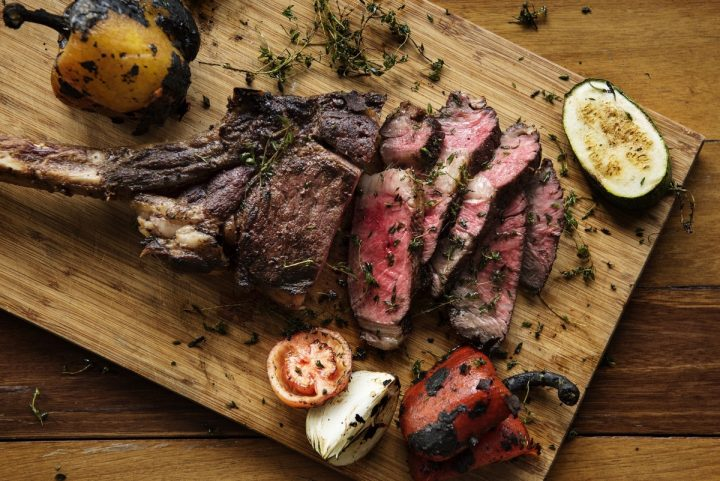 roast meat with herbs on wooden board