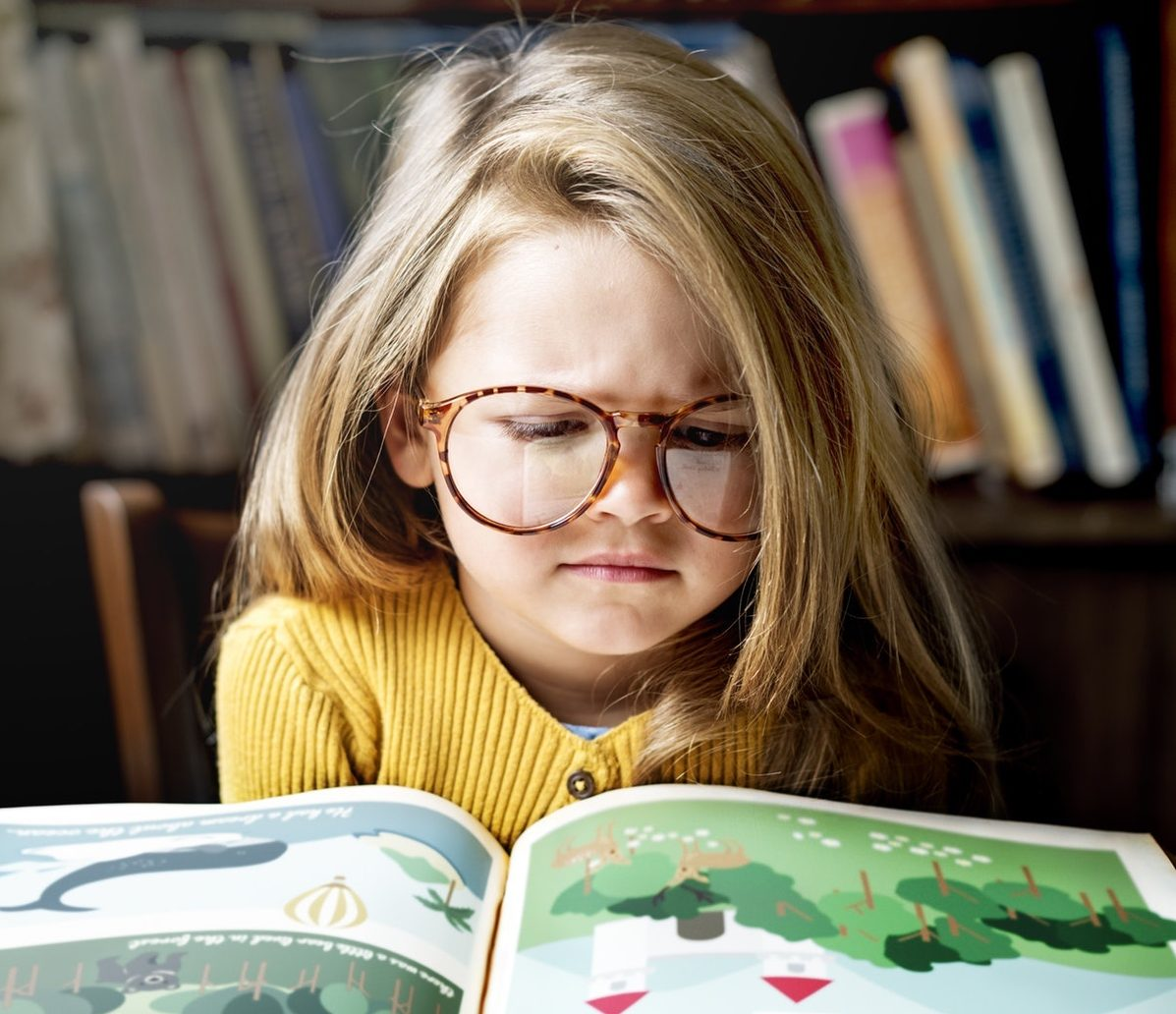 girl with glasses and yellow top reading story book
