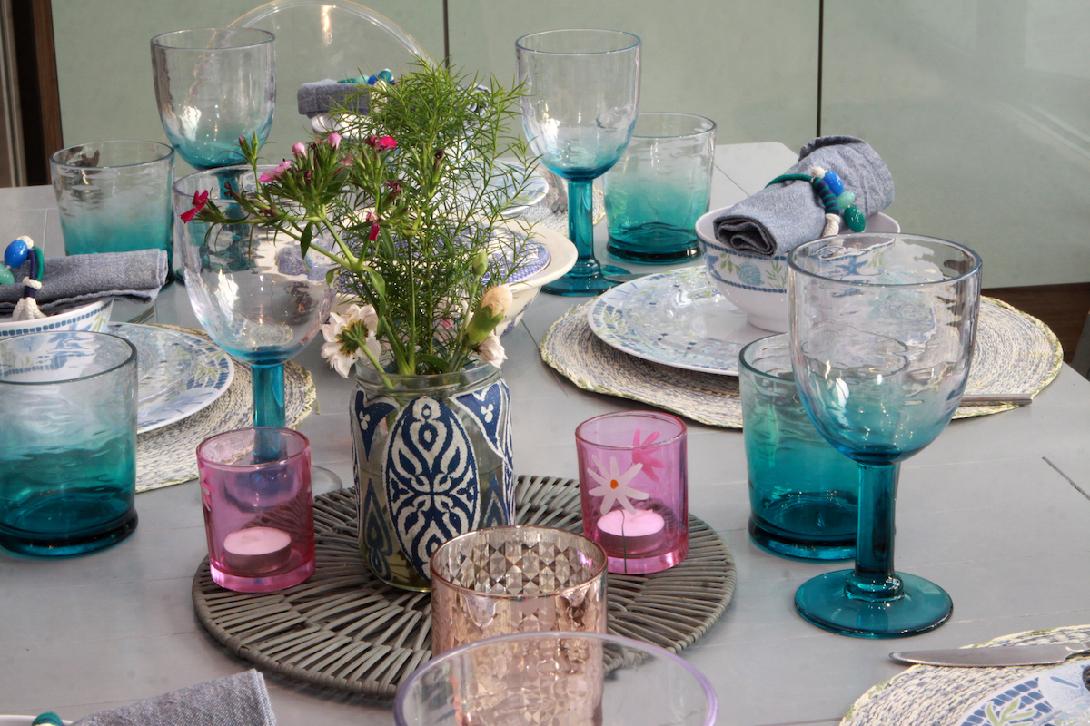 Table laid up with blue and pink glasses flowers and candles