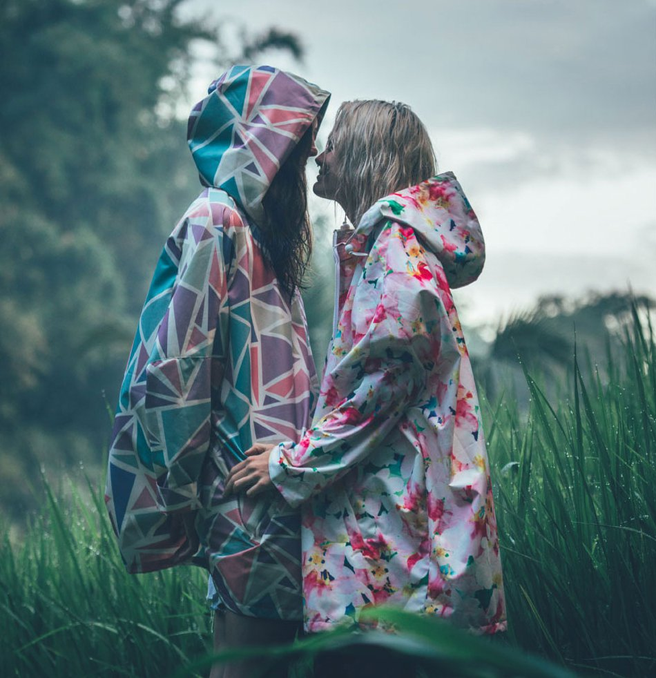 couple in raincoats in field